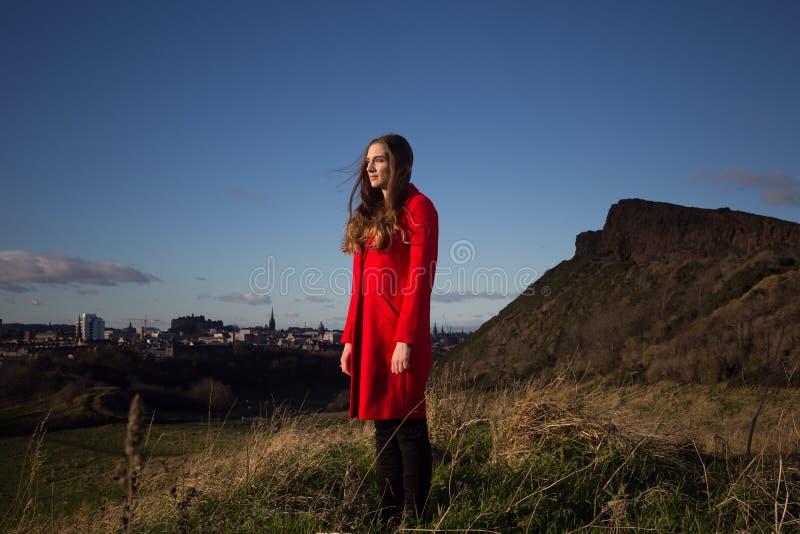 Aantrekkelijke jonge vrouw in rode laag in Holyrood-Park royalty-vrije stock fotografie