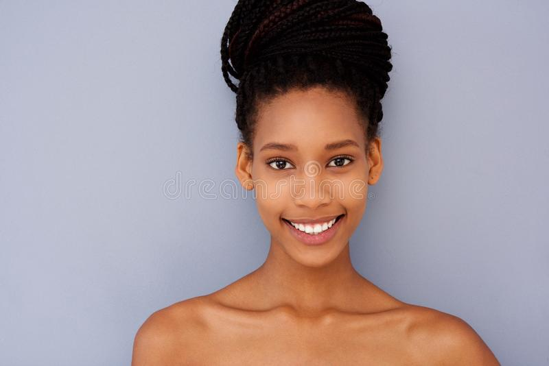 Aantrekkelijke jonge vrouw tegen grijze muur met naakte schouders stock afbeeldingen
