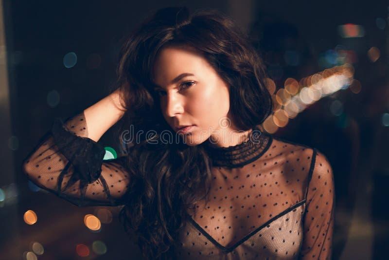 Aantrekkelijke jonge vrouw in zwarte cocktailkleding voor venster bij nacht stock foto's