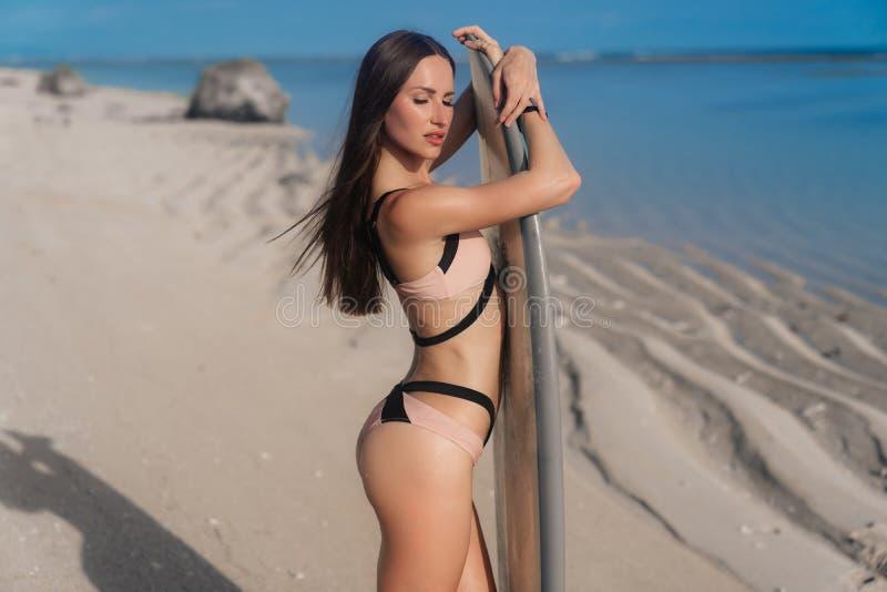 Aantrekkelijke jonge vrouw in zwempak die zich op strand met surfplank bevinden stock foto