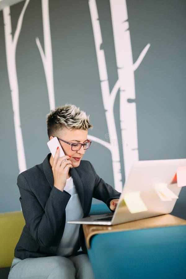 Aantrekkelijke jonge vrouwelijke architect die aan laptop werken stock foto