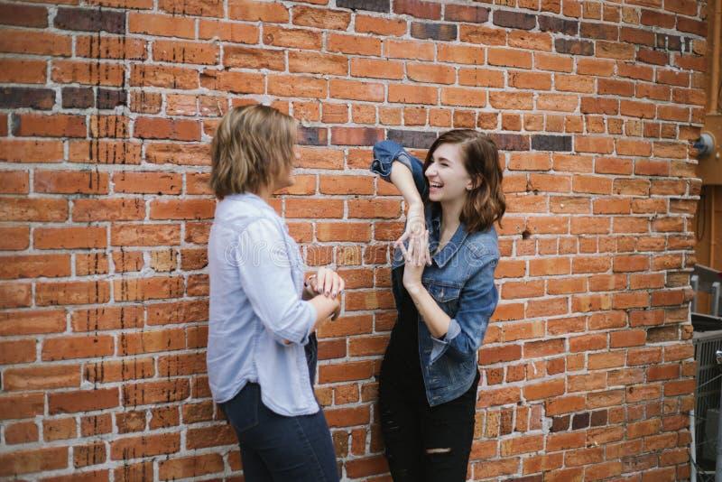 Aantrekkelijke Jonge Vrouwelijke Beste Vrienden die en Pret voor Baksteen Stedelijke Muur modelleren hebben stock fotografie