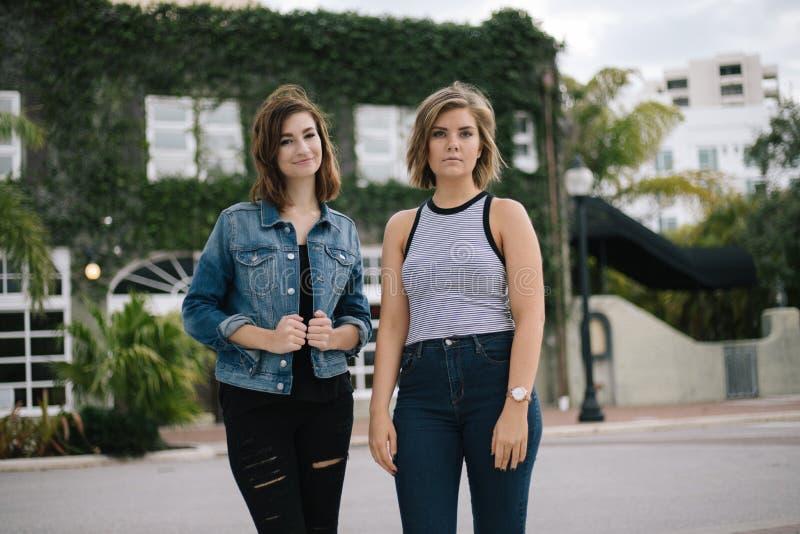 Aantrekkelijke Jonge Vrouwelijke Beste Vrienden die en Pret voor de Overwoekerde Stedelijke Bouw modelleren hebben stock afbeelding