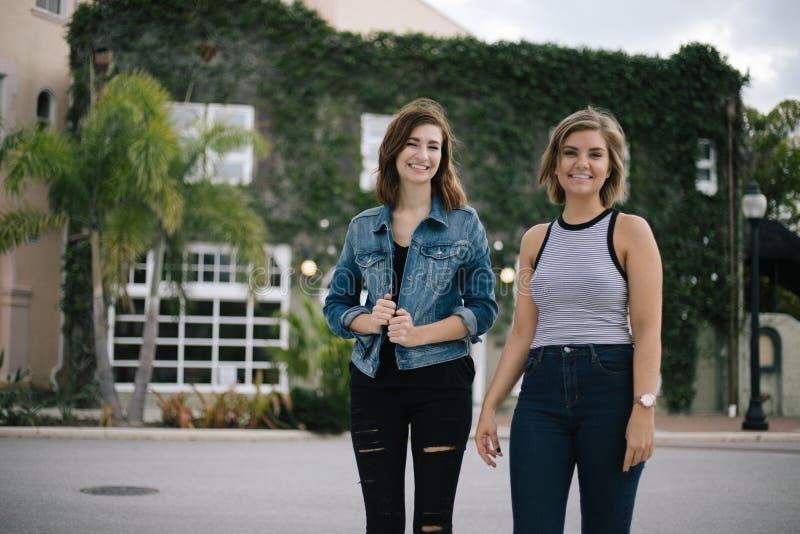 Aantrekkelijke Jonge Vrouwelijke Beste Vrienden die en Pret voor de Overwoekerde Stedelijke Bouw modelleren hebben stock fotografie