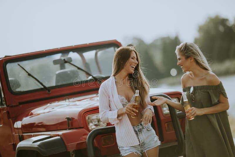 Aantrekkelijke jonge vrouwen die zich door een convertibele auto bevinden stock afbeelding