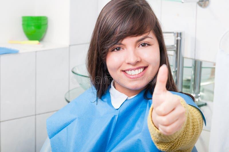 Aantrekkelijke jonge vrouwenduim omhoog in tandheelkundebureau stock afbeeldingen