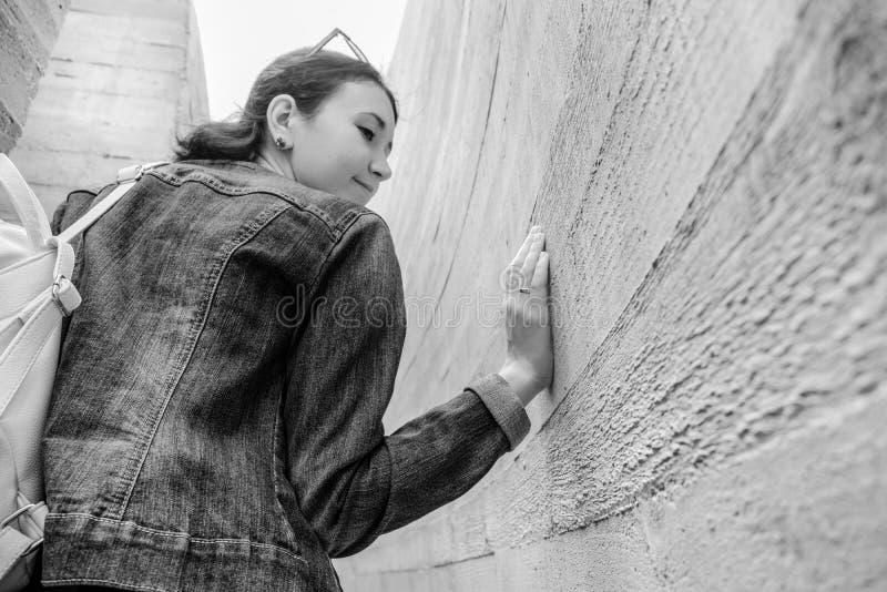 Aantrekkelijke jonge vrouwentribunes tussen concrete muren Het Kaukasische meisje in toevallige jeans en kleding kijkt terug royalty-vrije stock fotografie