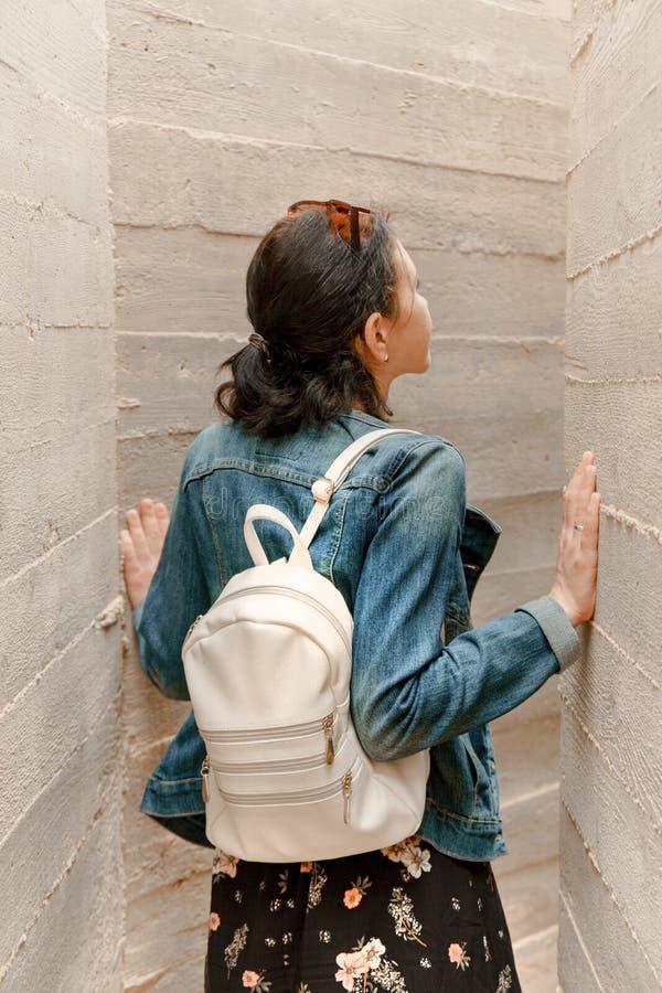 Aantrekkelijke jonge vrouwentribunes tussen concrete muren Het Kaukasische meisje in toevallige jeans kijkt omhoog stock fotografie