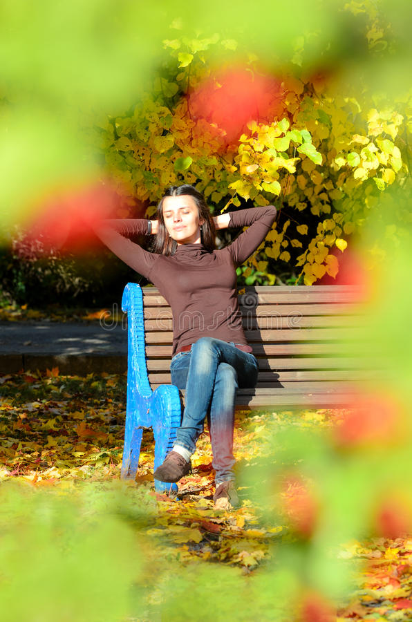 Aantrekkelijke jonge vrouwenzitting op bruine houten bank met handen achter haar hoofd in mooi park Zij sloot ogen royalty-vrije stock afbeelding