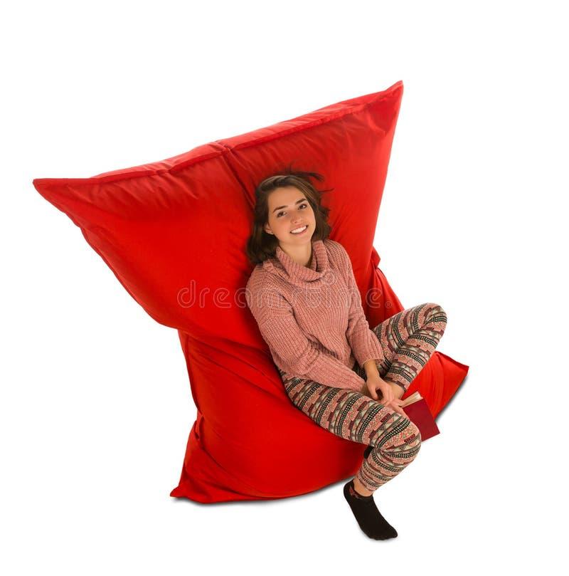Aantrekkelijke jonge vrouwenzitting op de rode stoel van de beanbagbank voor liv stock afbeeldingen