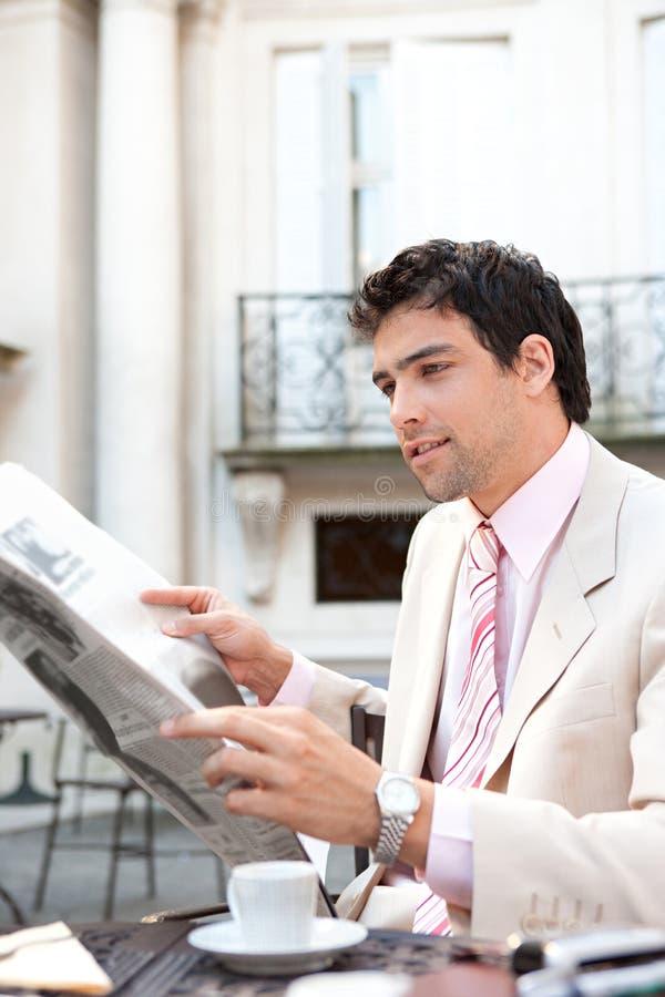 Het aantrekkelijke document van de zakenmanlezing in koffie. stock afbeeldingen