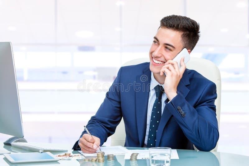 Aantrekkelijke jonge zakenman die op slimme telefoon in bureau spreken stock afbeelding