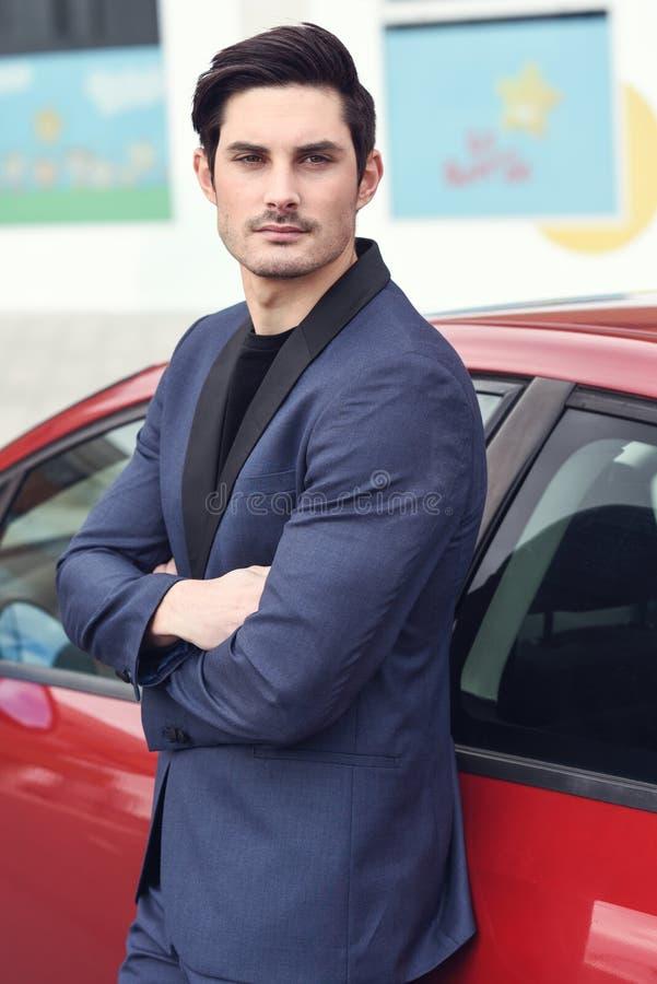 Aantrekkelijke jonge zakenman die zich dichtbij een rode auto bevinden stock foto's