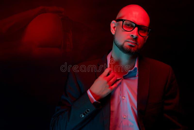 Aantrekkelijke kale mens met baard met glazen op neonlichtachtergrond stock afbeelding