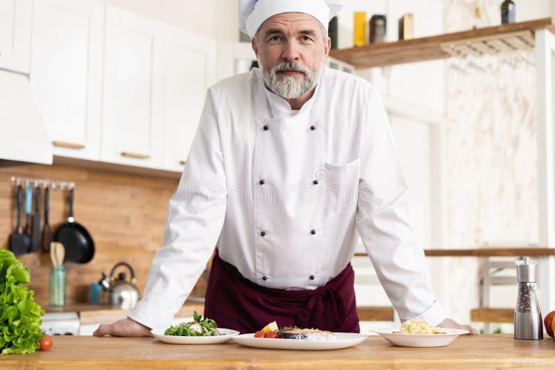 Aantrekkelijke Kaukasische chef-kok die zich in een restaurantkeuken bevinden stock foto's