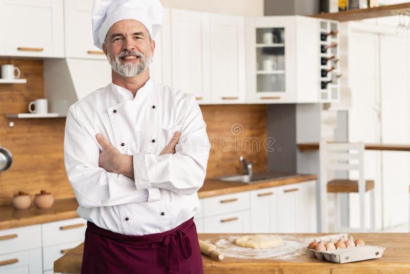 Aantrekkelijke Kaukasische chef-kok die zich met die wapens bevinden in een restaurantkeuken worden gekruist royalty-vrije stock foto's