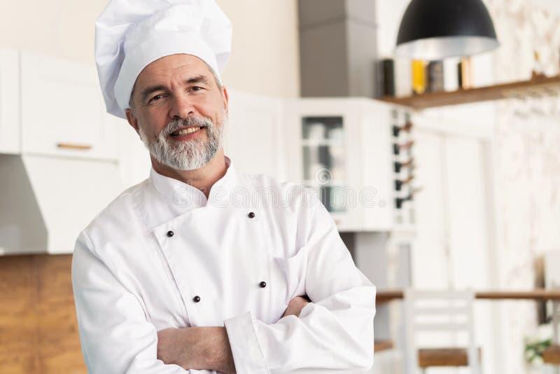 Aantrekkelijke Kaukasische chef-kok die zich met die wapens bevinden in een restaurantkeuken worden gekruist royalty-vrije stock afbeelding