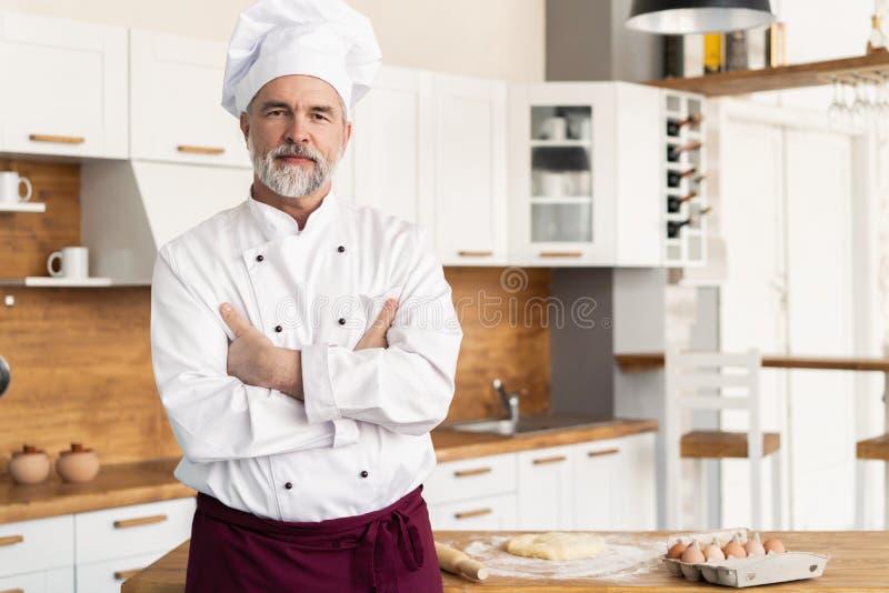 Aantrekkelijke Kaukasische chef-kok die zich met die wapens bevinden in een restaurantkeuken worden gekruist royalty-vrije stock foto