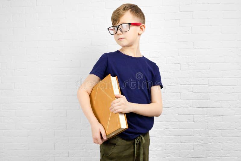 Aantrekkelijke Kaukasische jongen 10 jaar oude dragende oogglazen die in zijn handen groot boek houden stock fotografie
