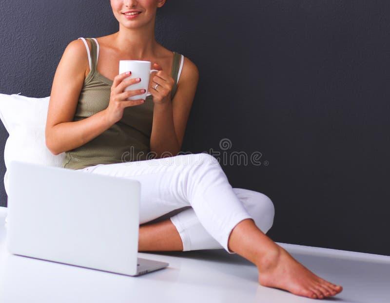 Aantrekkelijke Kaukasische meisjeszitting op vloer met laptop royalty-vrije stock foto's