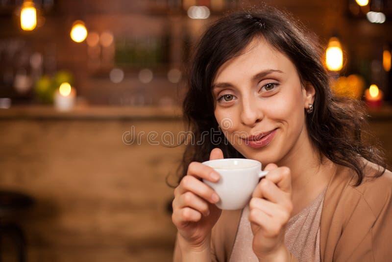 Aantrekkelijke Kaukasische vrouw die en de camera met een koffiekop ter beschikking smilling bekijken stock afbeelding