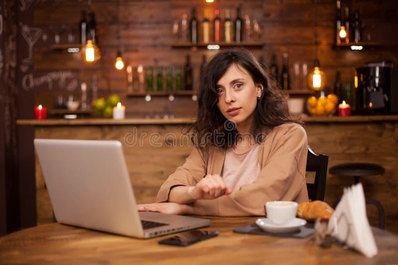 Aantrekkelijke Kaukasische vrouw die haar laptop in een koffiewinkel met behulp van met interent verbinding royalty-vrije stock afbeeldingen