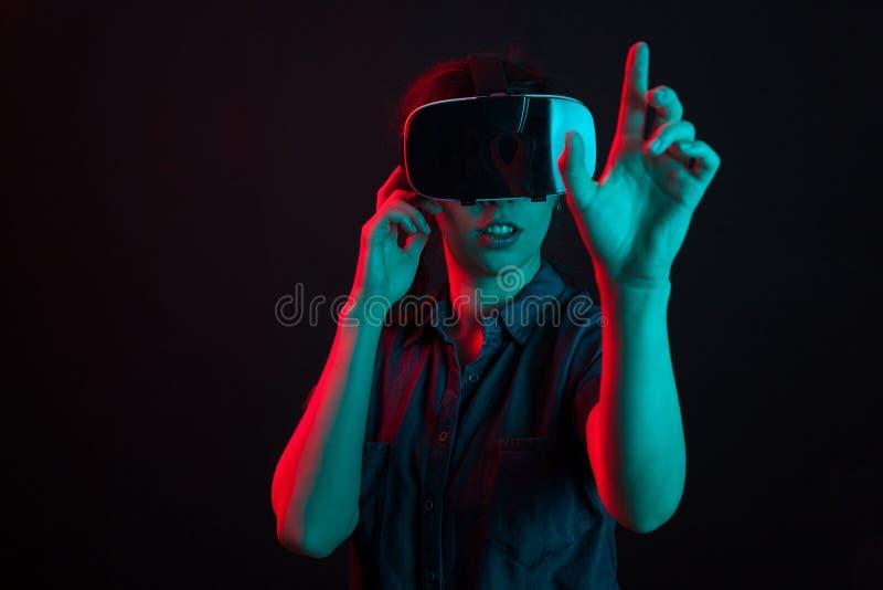 Aantrekkelijke Kaukasische vrouw die in studio met virtuele werkelijkheidshelm wordt verbaasd stock foto
