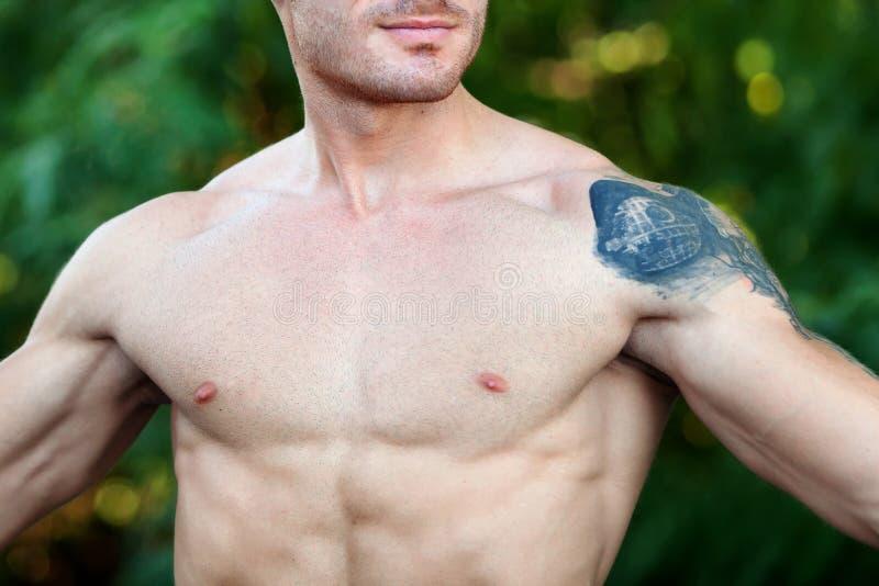 Aantrekkelijke kerel die zijn spieren en een grote tatoegering tonen stock afbeelding