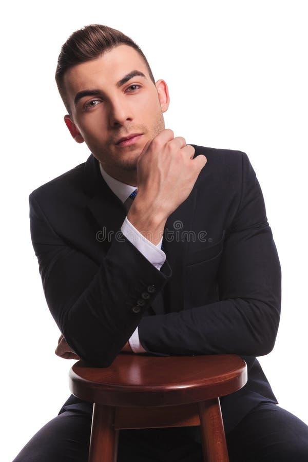 Aantrekkelijke kerel in kostuum met handen op stoel royalty-vrije stock foto