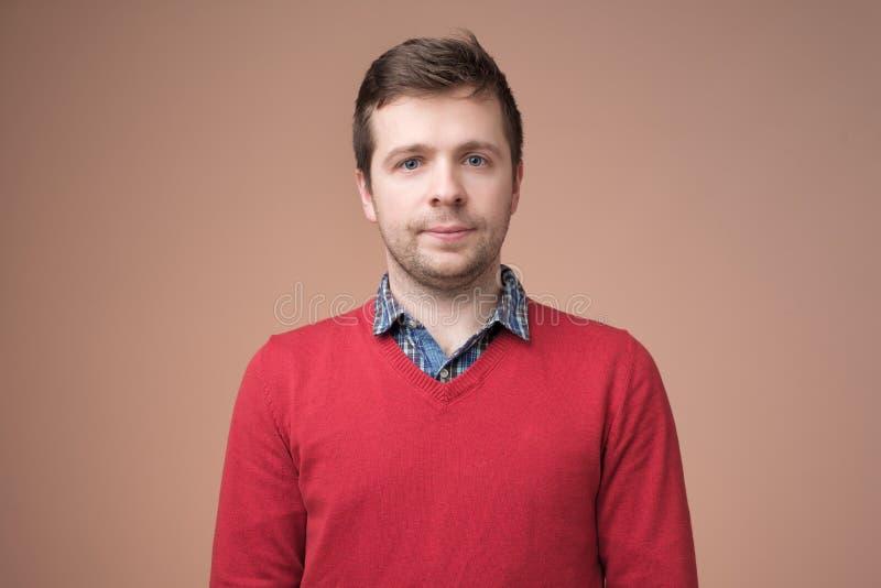 Aantrekkelijke knappe glimlachende positieve Kaukasische mens in rode sweater royalty-vrije stock afbeeldingen