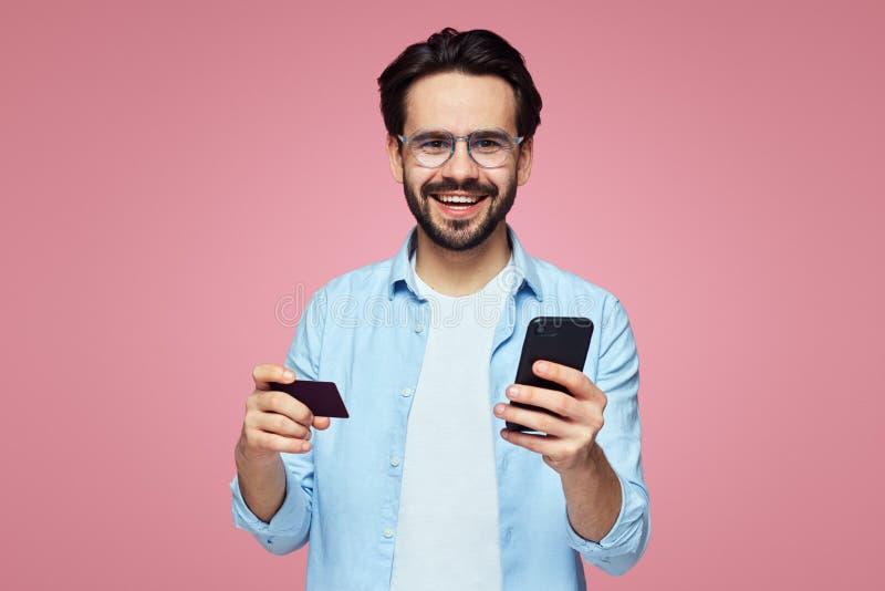 Aantrekkelijke knappe mens die terwijl het houden van plastic creditcard en mobiele die telefoon glimlachen, over roze achtergron royalty-vrije stock foto's