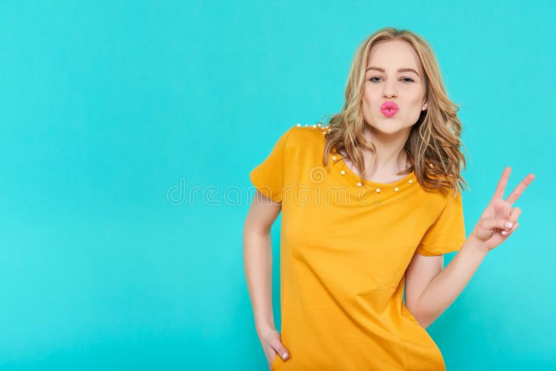 Aantrekkelijke koele jonge vrouw die een kus blazen en de handgebaar maken van het vredesteken stock foto's