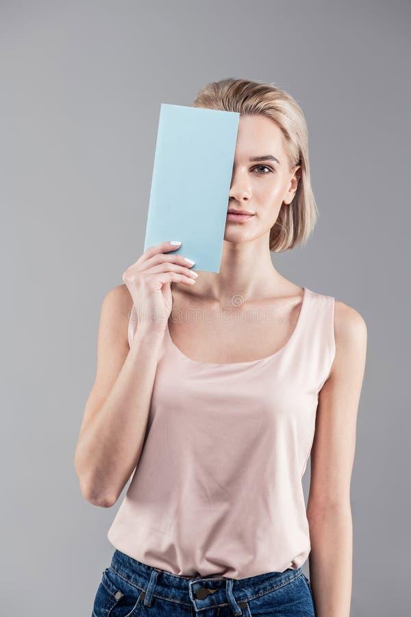 Aantrekkelijke kortharige vrouw in jeans en overhemd het sluiten de helft van haar gezicht royalty-vrije stock foto