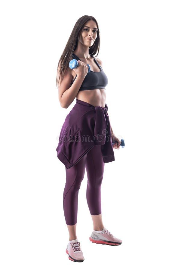 Aantrekkelijke Latijnse geschikte sportieve vrouw die bicep wapenoefeningen met domoor doen die camera bekijken stock foto's