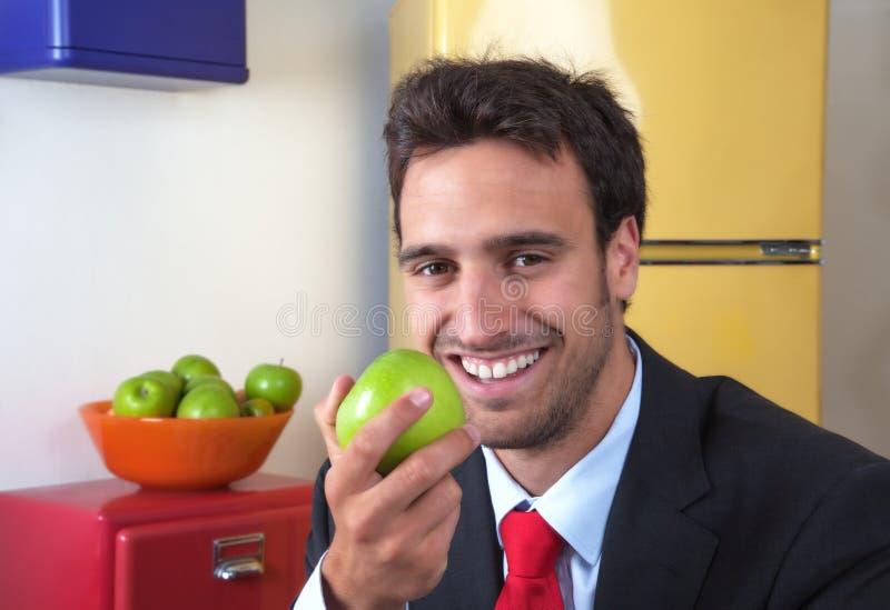Aantrekkelijke Latijnse mens die een appel eten stock foto