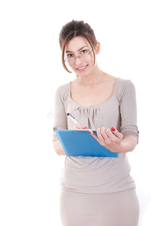 Aantrekkelijke leraar die glazen dragen die op haar klembord schrijven met royalty-vrije stock foto
