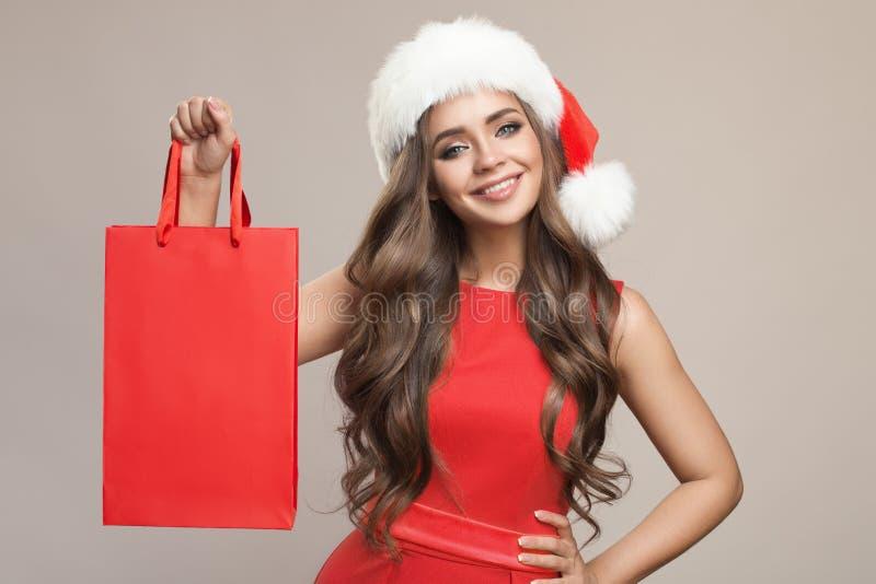 aantrekkelijke leuke vrouw in de holding van de santahoed het winkelen zak royalty-vrije stock fotografie