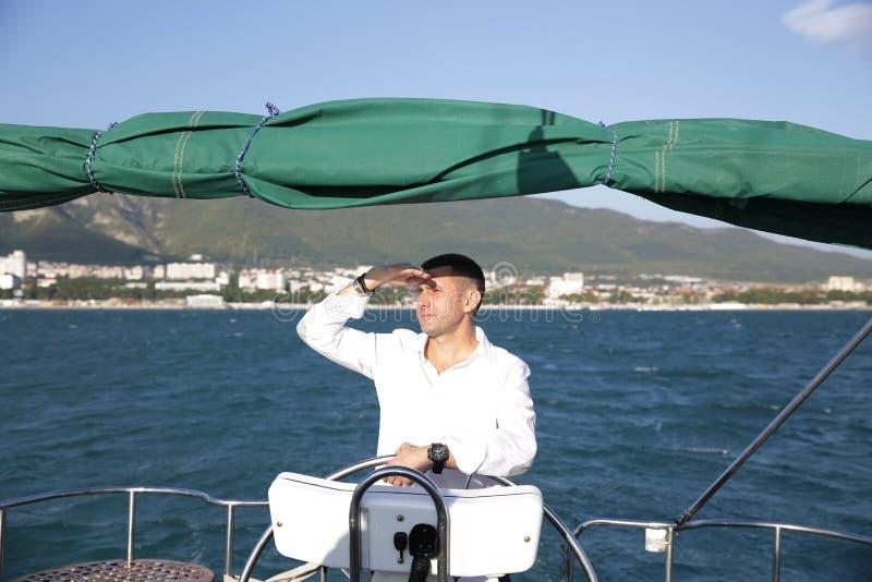 Aantrekkelijke man in witte tribunes aan het roer van een jacht op zee en kijkt naar de horizon met zijn hand opgevoed Sailing, t stock afbeelding