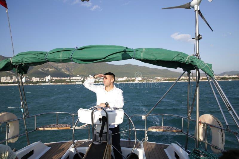 Aantrekkelijke man in witte tribunes aan het roer van een jacht op zee en kijkt naar de horizon met zijn hand opgevoed Sailing, t royalty-vrije stock fotografie
