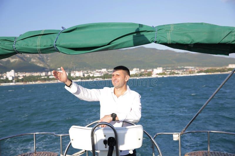 Aantrekkelijke man in witte tribunes aan het roer van een jacht op zee en kijkt naar de horizon met zijn hand opgevoed Sailing, t royalty-vrije stock foto's