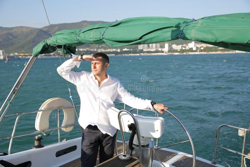 Aantrekkelijke man in witte tribunes aan het roer van een jacht op zee en kijkt naar de horizon met zijn hand opgevoed Sailing, t royalty-vrije stock afbeelding