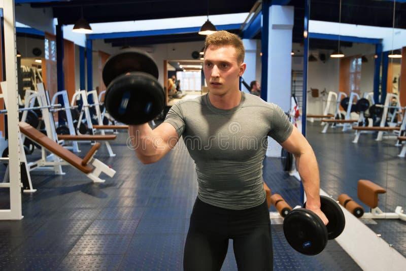 Aantrekkelijke mannelijke atleet die bicepsenoefening met domoren doen royalty-vrije stock afbeeldingen