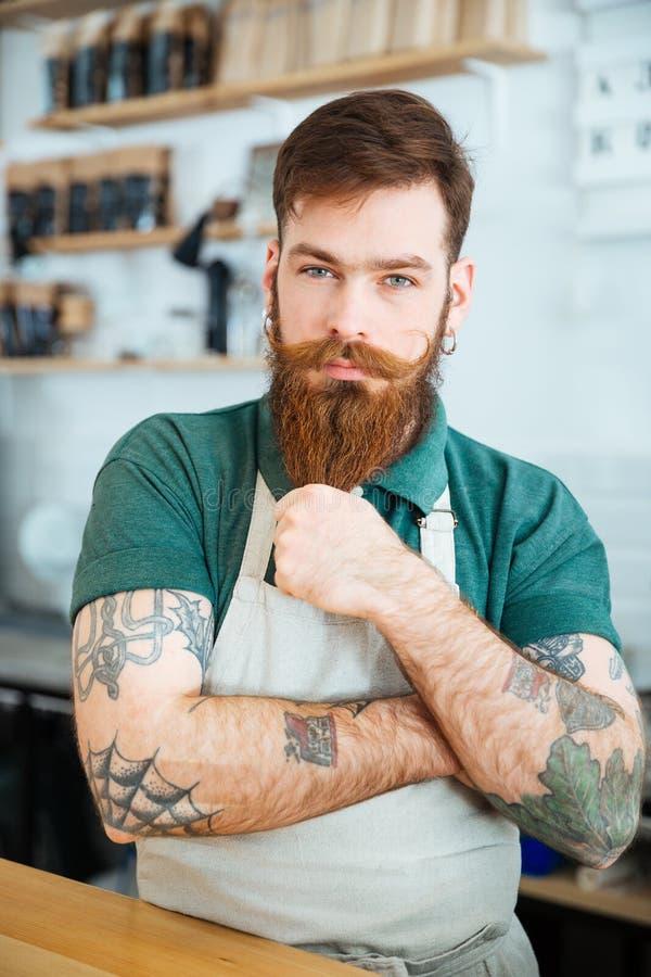 Aantrekkelijke mannelijke barista die en zich wat betreft zijn baard bevinden royalty-vrije stock foto