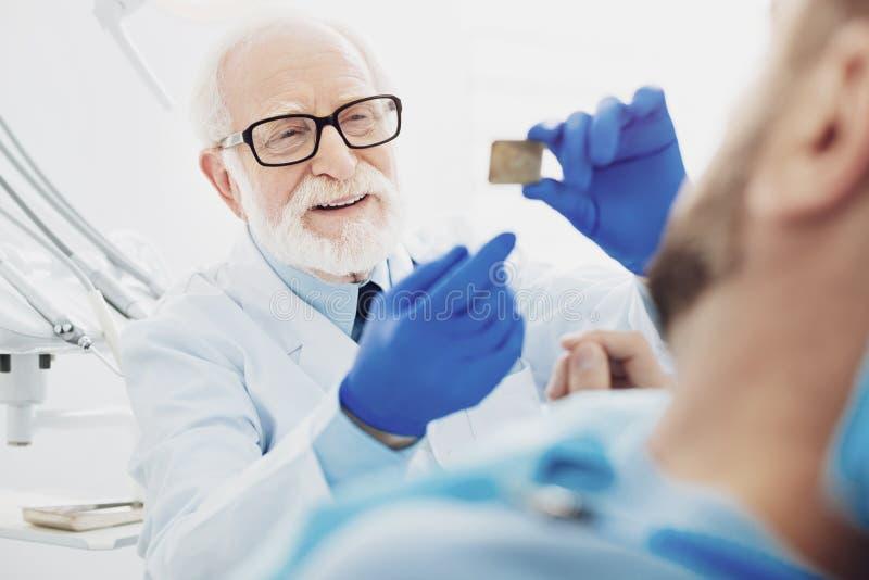 Aantrekkelijke mannelijke tandarts die verklaring geven stock afbeelding