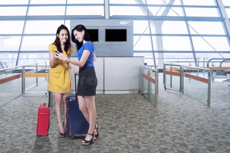 Aantrekkelijke meisjes met cellphone in luchthaven stock foto's
