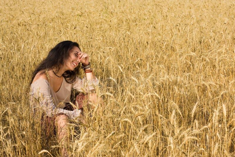 Aantrekkelijke meisjeszitting in gouden tarwe stock afbeelding