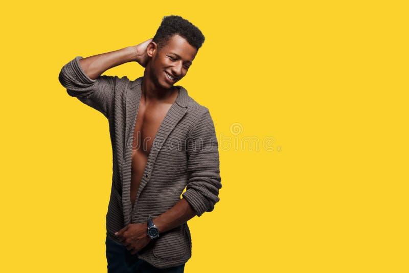 Aantrekkelijke mens in bruine cardigans, die hand houden dichtbij hoofd, op gele achtergrond, exemplaarruimte wordt ge?soleerd stock afbeelding