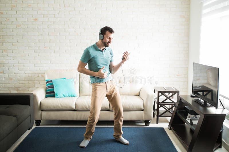 Aantrekkelijke mens die in de woonkamer dansen royalty-vrije stock fotografie