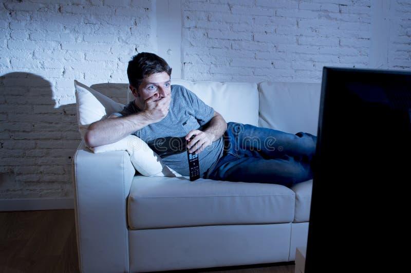Aantrekkelijke mens die thuis op laag bij woonkamer die verrast op TV letten kijkend in schok liggen royalty-vrije stock fotografie