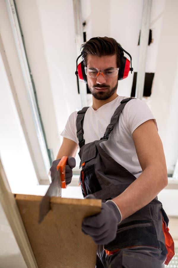 Aantrekkelijke mens die wat houtbewerking doen stock fotografie